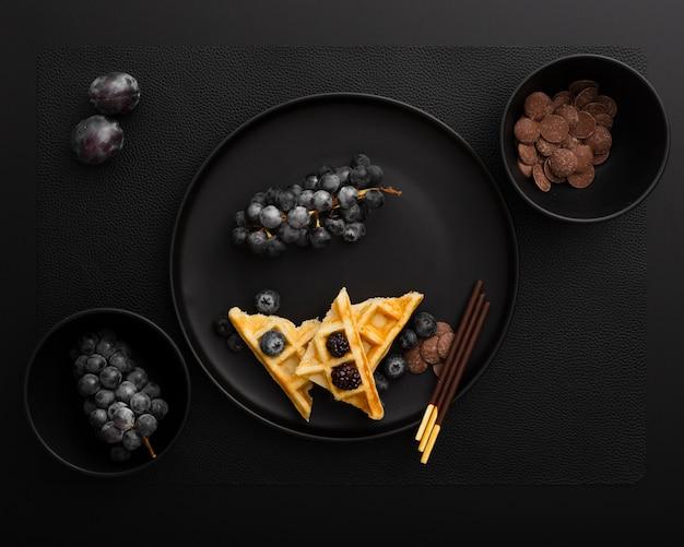 Donkere plaat met wafels en druiven op een donkere achtergrond Gratis Foto
