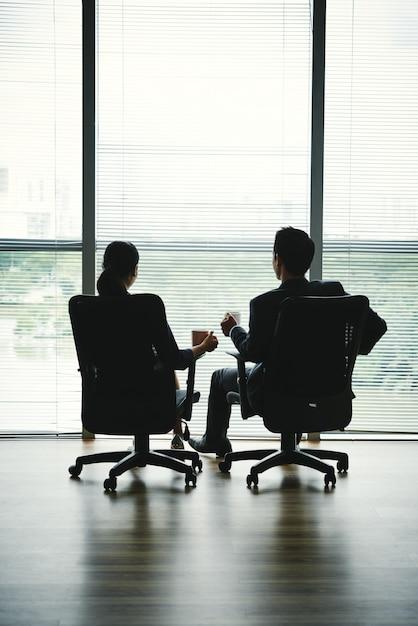 Donkere silhouetten van man en vrouw zitten met mokken in bureaustoelen voor raam Gratis Foto
