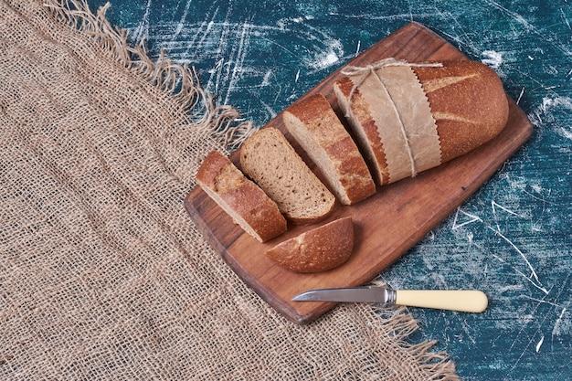 Donkere sneetjes brood op een houten bord. Gratis Foto