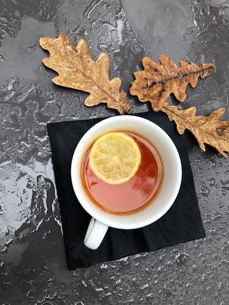 Donkere tafel met druppels water na regen en herfstbladeren met een mok thee met citroenen. Premium Foto