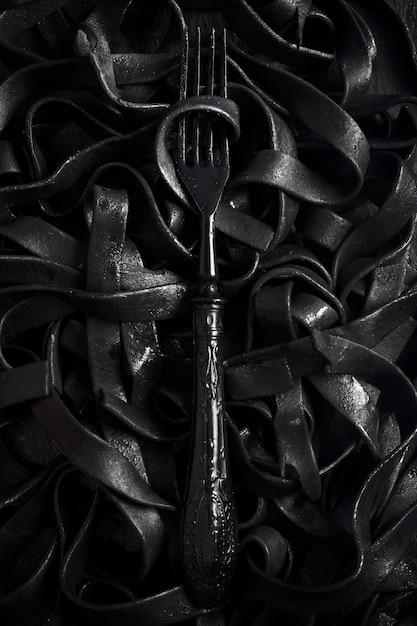 Donkere tagliatelledeegwaren met vork Gratis Foto