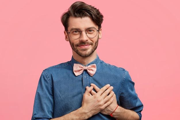 Donkerharige man met roze bowtie en denim overhemd Gratis Foto
