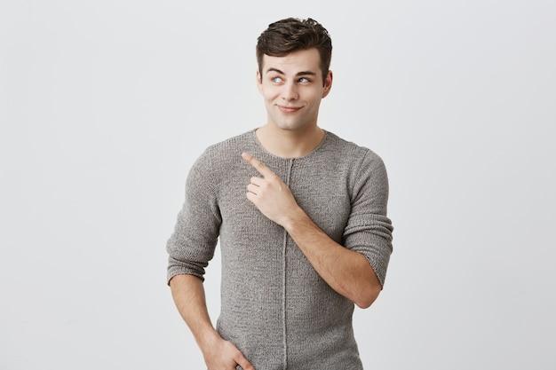 Donkerharige stijlvolle man in trui kijken met zijn blauwe ogen opzij wijzend met wijsvinger op kopie ruimte reclame iets. man poseren tegen muur met kopie ruimte voor tekst of promotie Gratis Foto