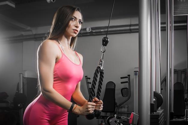 Donkerharige vrouw atleet in een trainingspak schudt hand-triceps biceps op een simulator in de sportschool. Premium Foto