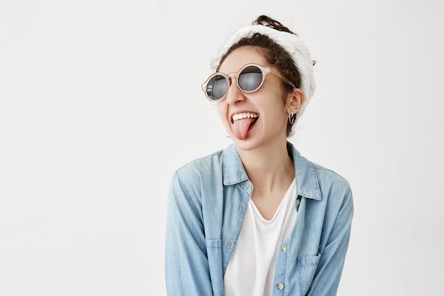Donkerharige vrouwelijke meid met do-rag, draagt een ronde zonnebril en een spijkerblouse, heeft zijn eigen specifieke stijl, steekt zijn tong uit, maakt grimas, heeft plezier. emoties en gezichtsuitdrukking concept Gratis Foto