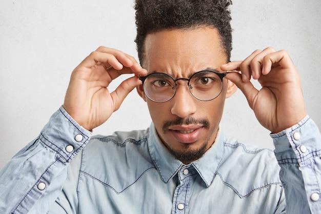 Donkerhuidige afro-amerikaanse man ziet er streng uit door een bril, draagt een spijkerblouse Gratis Foto
