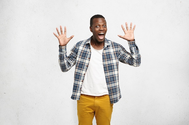 Donkerhuidige jonge man in stijlvolle kleding die groetgebaar toont of high five geeft met beide handen, kijkend met een opgewonden en opgewonden uitdrukking. lichaamstaal Gratis Foto