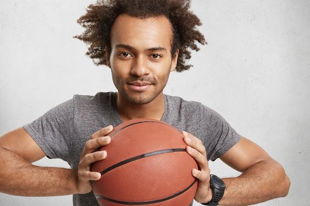 Donkerhuidige man van gemengd ras adverteert basketbal Gratis Foto