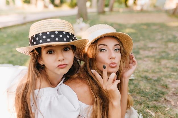 Donkerogige meisje in hoed gek rond met moeder genieten van familieweekend in groen park. sierlijke vrouw draagt elegante ring grappige gezichten maken en een grapje maken met dochter buiten rusten. Gratis Foto