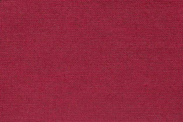 Donkerrode achtergrond van een textielproduct met rieten patroon, close-up. Premium Foto
