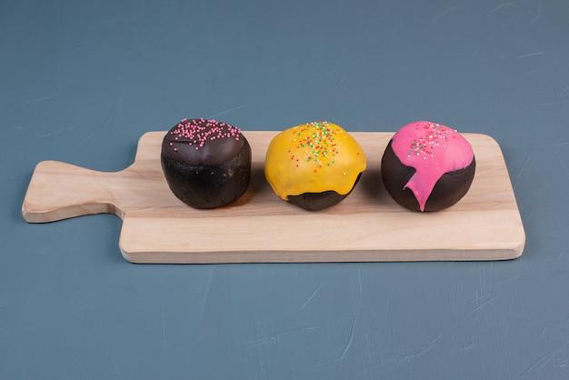 Donut drie op een houten bord. Gratis Foto