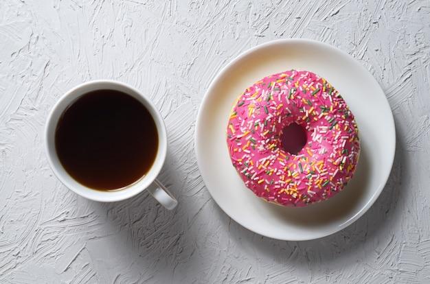 Donut met kleurrijke suikerglazuur en kopje koffie op lichtgrijze stenen achtergrond Premium Foto