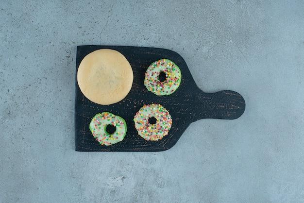 Donuts en een koekje op een zwarte bord op marmeren achtergrond. hoge kwaliteit foto Gratis Foto
