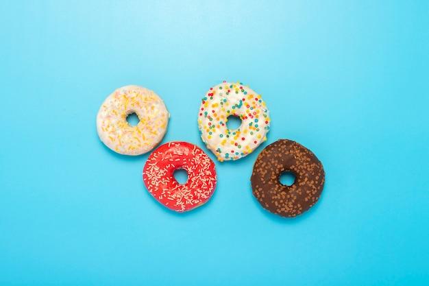 Donuts van verschillende typen op een blauwe ruimte. concept van snoep, bakkerij ,. banner. plat lag, bovenaanzicht. Premium Foto