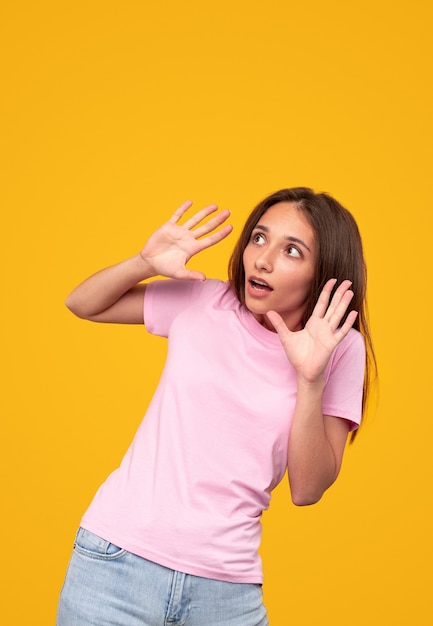 Doodsbange jonge vrouw in vrijetijdskleding die gebarend en wegkijkend terwijl ze probeerde gevaar te ontwijken tegen een gele achtergrond Premium Foto
