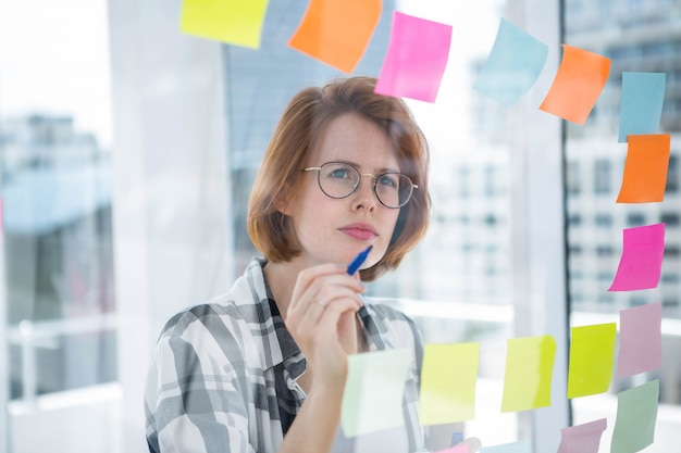 Doordachte hipster vrouw, staande in haar kantoor, het lezen van notities over het geheel Premium Foto