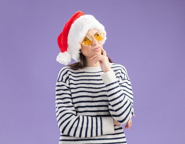 Doordachte jonge blanke meisje in zonnebril met kerstmuts legt hand op de kin en kijkt naar de zijkant Gratis Foto