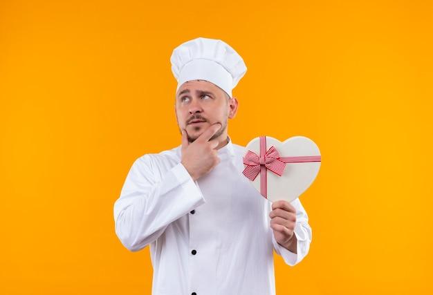 Doordachte jonge knappe kok in chef-kok uniforme bedrijf hartvormige geschenkdoos met hand op kin kant geïsoleerd op oranje ruimte kijken Gratis Foto