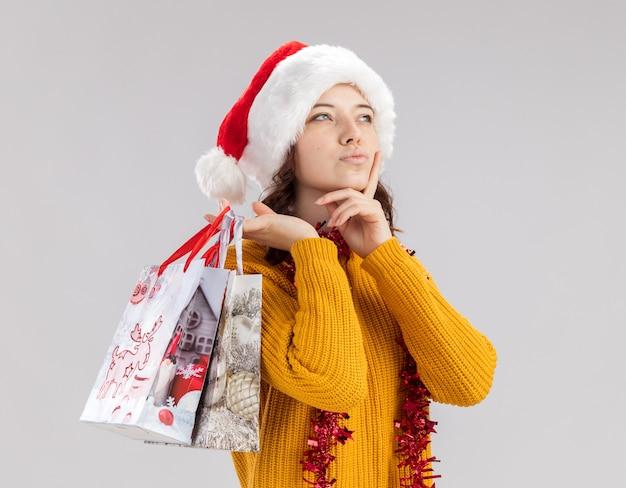 Doordachte jonge slavische meisje met kerstmuts en met slinger rond nek legt hand op kin en houdt papieren geschenkzakken kant kijken Gratis Foto