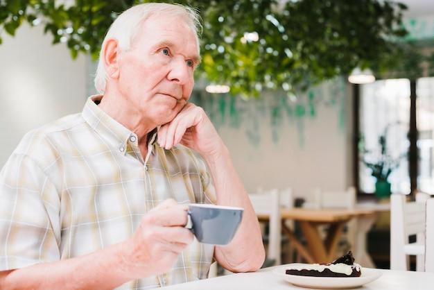 Doordachte oudere man het drinken van thee Gratis Foto
