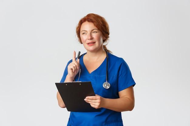 Doordachte roodharige vrouwelijke arts, roodharige arts in blauwe scrubs op zoek geïntrigeerd door patiëntgeval, pen schudden en klembord vasthouden Gratis Foto