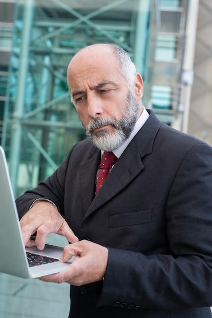 Doordachte volwassen man met laptop op straat Gratis Foto