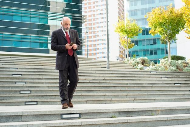 Doordachte volwassen man met telefoon tijdens het lopen naar beneden op de trap Gratis Foto