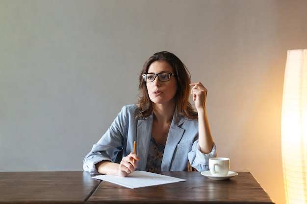 Doordachte vrouw schrijven van notities. Gratis Foto