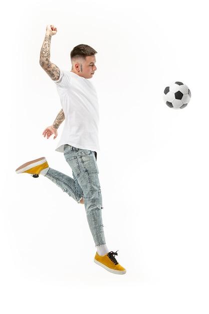 Doorsturen naar de overwinning. jonge man als voetballer springen en schoppen de bal in studio op een witte achtergrond. voetbalfan en wereldkampioenschap concept. Gratis Foto