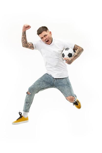Doorsturen naar de overwinning. jonge man als voetballer springen en schoppen de bal in studio op een witte achtergrond. Gratis Foto