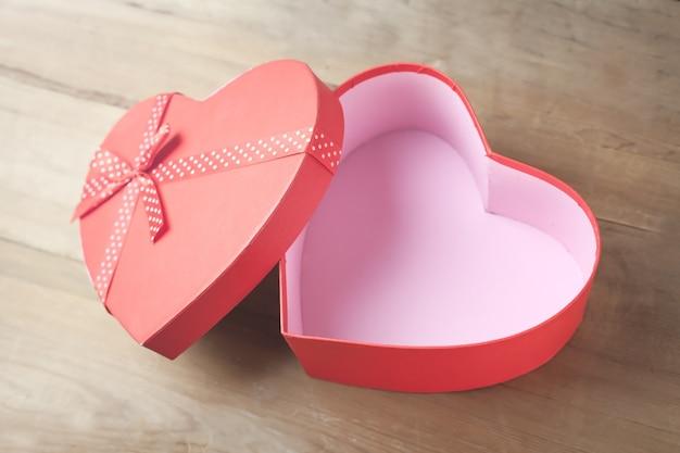 Doos in de vorm van hart op houten achtergrond. Premium Foto