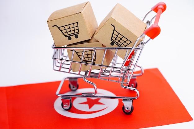 Doos met winkelwagen logo op tunesië vlag. Premium Foto