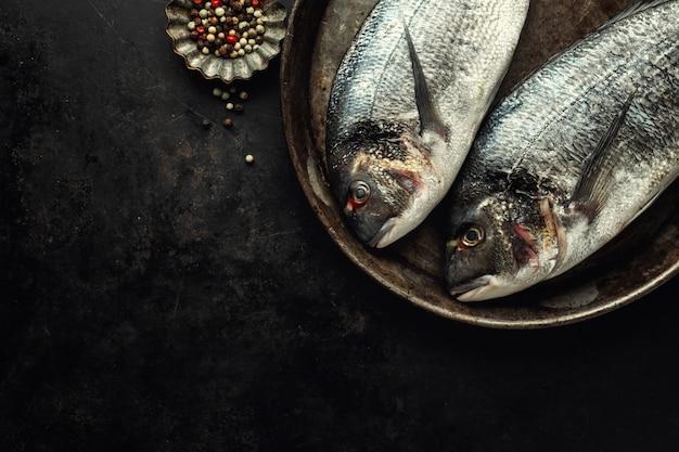 Doradovissen met ingrediënten op dark Premium Foto