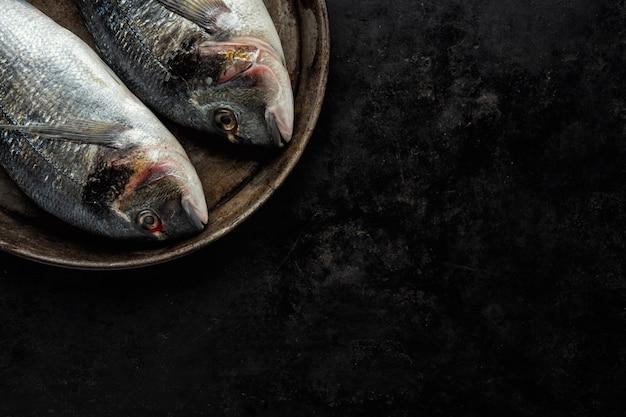 Doradovissen met ingrediënten op dark Gratis Foto