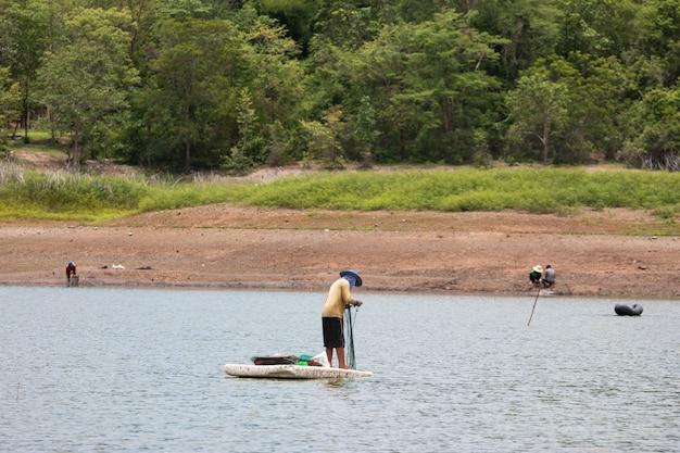 Dorpelingen zijn op zoek naar vis op het land met droge en gebarsten grond omdat droogte opwarming van de aarde. Premium Foto