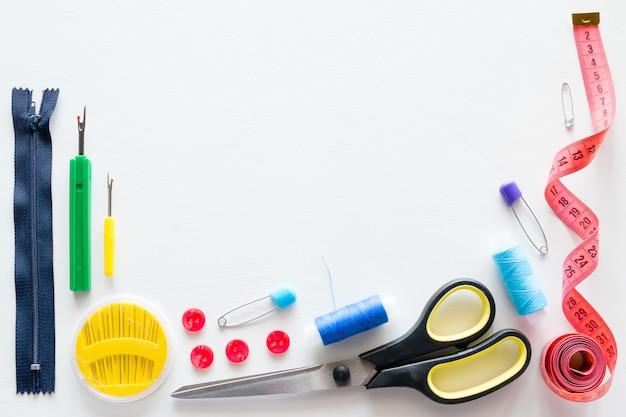Draad en naaien accessoires op wit met plaats voor tekst Premium Foto
