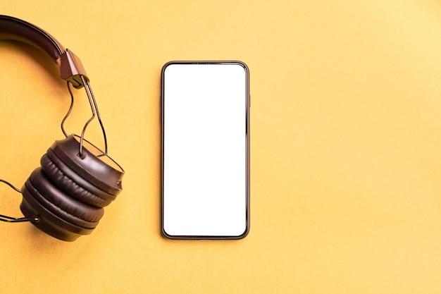 Draadloze zwarte hoofdtelefoons en frameloze smartphone op kleurrijke gele achtergrond Premium Foto