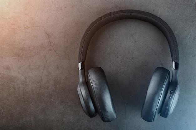 Draadloze zwarte koptelefoon op een donkere achtergrond met blauwe en oranje achtergrondverlichting Premium Foto