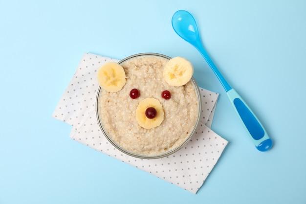 Draag gezicht van havermoutpap en vruchten op blauwe achtergrond, hoogste mening wordt gemaakt die. babyvoedsel Premium Foto