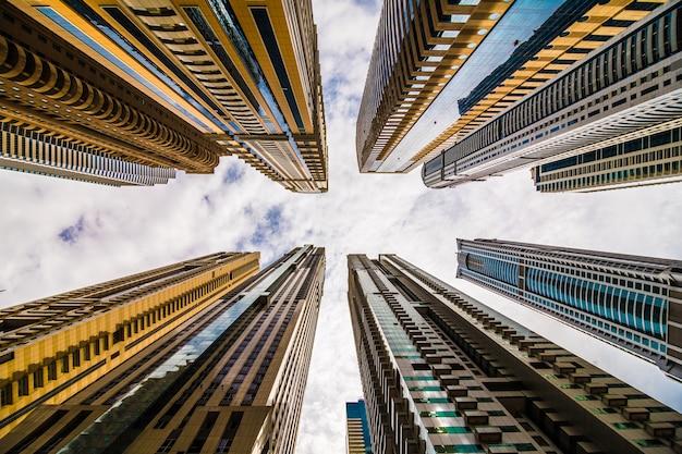 Dramatisch perspectief met lage hoekmening van wolkenkrabbers die omhoog naar de hemel kijken, dubai. verdwijnpunt Gratis Foto
