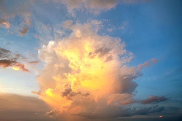 Dramatische cloudscape met gezwollen wolken verlicht door oranje ondergaande zon en blauwe hemel. Premium Foto