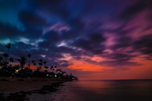 Dramatische zonsondergang over het exotische strand, met palmen. Premium Foto