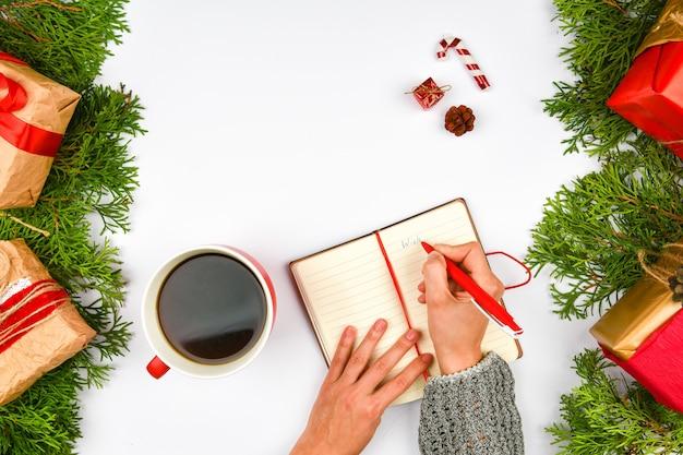 Dreams of goal plans maken een lijst voor het schrijven van een nieuwjaars-kerstconcept in een notitieboekje Premium Foto