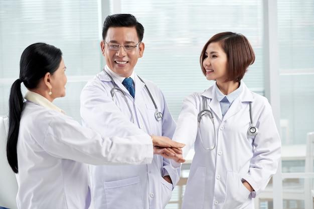 Drie artsen geven eenheid gebaar symboliseert teamwerk Gratis Foto