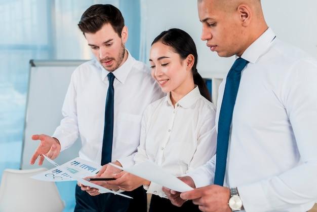 Drie bedrijfsleiders die het businessplan in het bureau bespreken Gratis Foto