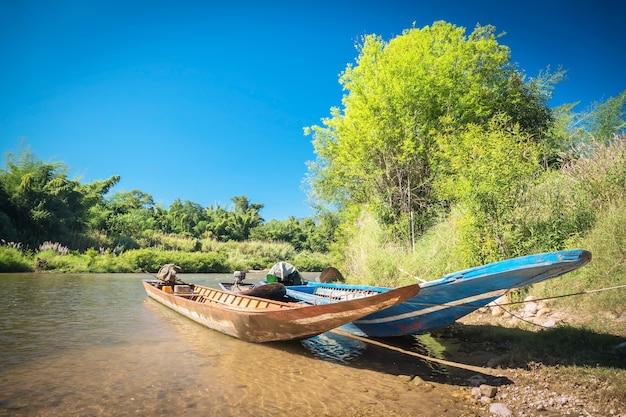 Drie boten werden vastgebonden in de rivier met blauwe hemelachtergrond Premium Foto