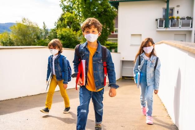 Drie broers met gezichtsmaskers klaar om terug naar school te gaan. nieuwe normaliteit, sociale afstand, coronavirus-pandemie, covid-19. van huis weggaan Premium Foto