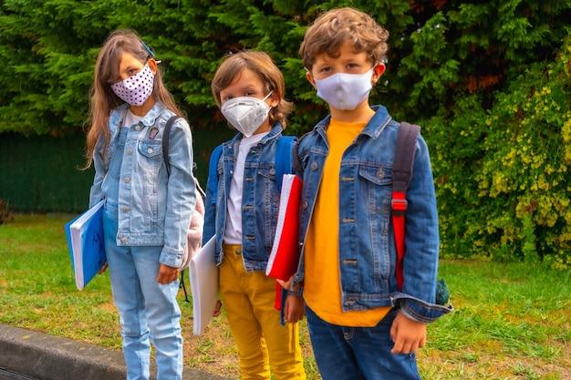 Drie broers met gezichtsmaskers klaar om terug naar school te gaan. nieuwe normaliteit, sociale afstand, coronavirus-pandemie, covid-19. wachten om naar school te gaan met groene planten op de achtergrond Premium Foto