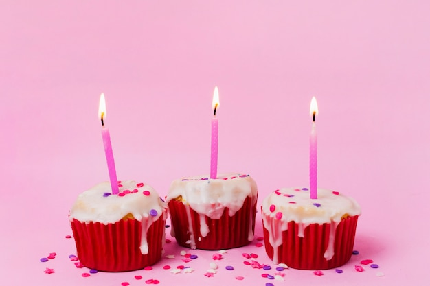 Drie cupcakes met aangestoken kaarsen Gratis Foto