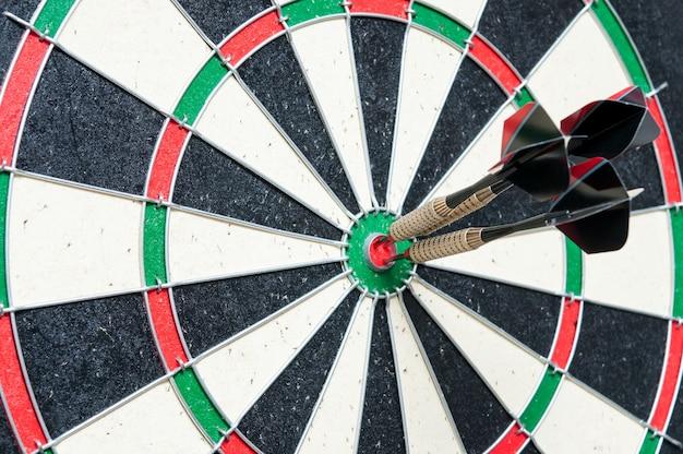 Drie darts in het midden van het dartbord Premium Foto